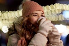 Mujer feliz con café sobre luces de la Navidad Imágenes de archivo libres de regalías