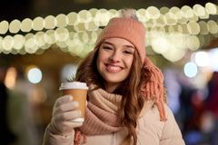 Mujer feliz con café sobre luces de la Navidad Foto de archivo