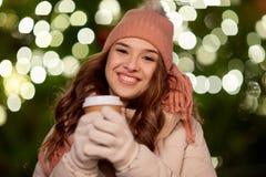 Mujer feliz con café sobre luces de la Navidad Foto de archivo libre de regalías