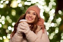 Mujer feliz con café sobre luces de la Navidad Fotos de archivo libres de regalías