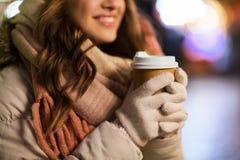 Mujer feliz con café sobre luces de la Navidad Fotos de archivo