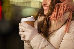 Mujer feliz con café sobre luces de la Navidad Fotografía de archivo