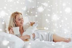 Mujer feliz con café y el gato en cama en casa Imagen de archivo libre de regalías