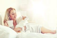 Mujer feliz con café y el gato en cama en casa Imágenes de archivo libres de regalías