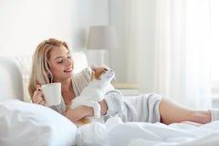 Mujer feliz con café y el gato en cama en casa Imagen de archivo