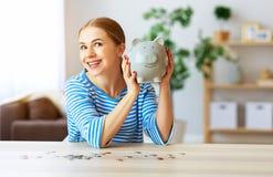 Mujer feliz con el banco guarro del dinero en fondo rosado Concepto de la planificaci?n financiera fotos de archivo