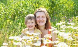 Mujer feliz con el bebé en planta de la margarita Fotos de archivo