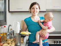 Mujer feliz con el bebé que cocina los purés de patata Foto de archivo libre de regalías