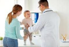 Mujer feliz con el bebé y el doctor en la clínica Imagen de archivo libre de regalías