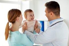 Mujer feliz con el bebé y el doctor en la clínica Fotos de archivo