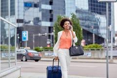 Mujer feliz con el bolso del viaje que invita a smartphone Imagenes de archivo