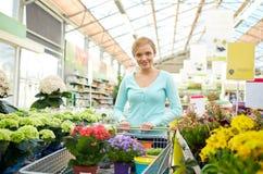 Mujer feliz con el carro de la compra y las flores en tienda Imagen de archivo libre de regalías