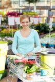 Mujer feliz con el carro de la compra y las flores en tienda Fotografía de archivo