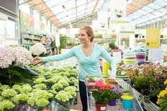 Mujer feliz con el carro de la compra y las flores en tienda Fotos de archivo