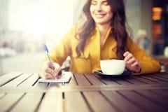 Mujer feliz con el cuaderno y cappucino en el café Imagenes de archivo