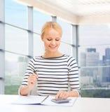 Mujer feliz con el cuaderno y la calculadora Imágenes de archivo libres de regalías