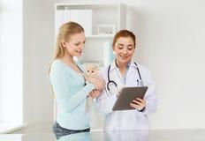 Mujer feliz con el gato y el doctor en la clínica del veterinario imágenes de archivo libres de regalías