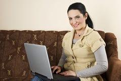 Mujer feliz con el hogar de la computadora portátil Fotografía de archivo