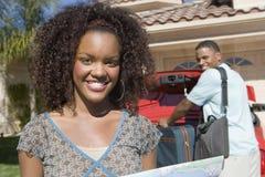 Mujer feliz con el hombre que mantiene el equipaje coche Fotos de archivo libres de regalías