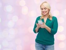 Mujer feliz con el mensaje que manda un SMS del smartphone Imagen de archivo