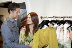 Mujer feliz con el novio que mira uno a en boutique de la ropa de moda imágenes de archivo libres de regalías