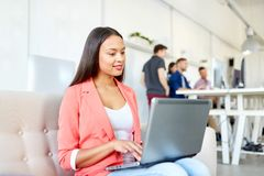 Mujer feliz con el ordenador portátil que trabaja en la oficina imágenes de archivo libres de regalías