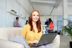 Mujer feliz con el ordenador portátil que trabaja en la oficina fotografía de archivo