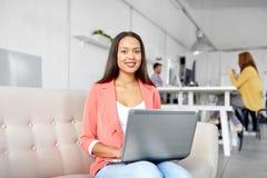 Mujer feliz con el ordenador portátil que trabaja en la oficina imagenes de archivo
