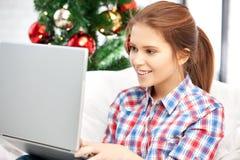 Mujer feliz con el ordenador portátil y el árbol de navidad Foto de archivo