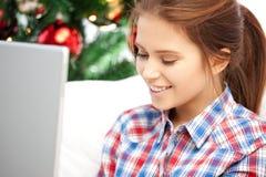 Mujer feliz con el ordenador portátil y el árbol de navidad Imágenes de archivo libres de regalías