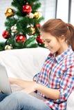 Mujer feliz con el ordenador portátil y el árbol de navidad Imagen de archivo