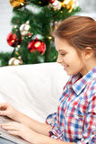 Mujer feliz con el ordenador portátil y el árbol de navidad Imagenes de archivo