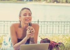 Mujer feliz con el ordenador portátil y el teléfono móvil que se relajan en un parque imagen de archivo