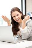 Mujer feliz con el ordenador y el dinero euro del efectivo Imagen de archivo