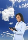 Mujer feliz con el ordenador y las nubes de la tablilla Imagen de archivo