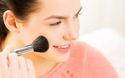 Mujer feliz con el pómulo de ruborización del cepillo del maquillaje Imagen de archivo libre de regalías