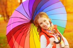 Mujer feliz con el paraguas multicolor del arco iris debajo de la lluvia en par imágenes de archivo libres de regalías