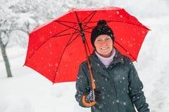 Mujer feliz con el paraguas rojo que goza de nieve del invierno foto de archivo