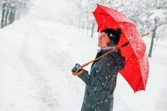 Mujer feliz con el paraguas rojo que goza de nieve del invierno fotografía de archivo