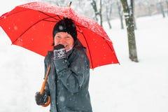 Mujer feliz con el paraguas rojo que goza de nieve del invierno imagen de archivo libre de regalías