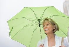 Mujer feliz con el paraguas verde contra el cielo claro fotos de archivo