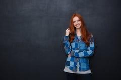 Mujer feliz con el pelo rojo que se coloca sobre fondo de la pizarra Foto de archivo