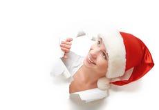 Mujer feliz con el sombrero de la Navidad que mira a escondidas a través de un agujero rasgado en cartel del Libro Blanco Fotografía de archivo