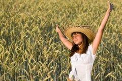 Mujer feliz con el sombrero de paja en campo de maíz Foto de archivo libre de regalías