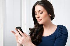 Mujer feliz con el teléfono elegante foto de archivo