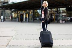 Mujer feliz con equipaje rodado que camina hacia la estación de tren Imagen de archivo libre de regalías