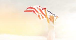 Mujer feliz con la bandera americana al aire libre Fotografía de archivo libre de regalías