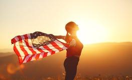 Mujer feliz con la bandera de Estados Unidos que disfruta de la puesta del sol en el na Imagenes de archivo