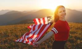 Mujer feliz con la bandera de Estados Unidos que disfruta de la puesta del sol en el na Imagen de archivo