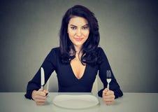 Mujer feliz con la bifurcación y cuchillo que se sienta en la tabla con la placa vacía fotos de archivo
